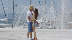 Happy affectionate couple cooling off near a water fountain in the city - stock footage