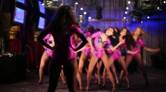 Back of teacher looking of nine dancing showgirls in costumes Stock Footage