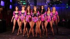 Ten beautiful showgirls in purple costumes dance in night club - stock footage