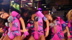 Eight pretty showgirls in pink costumes dance in night club - stock footage