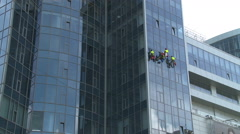 Window cleaners on the wall of a skyscraper. Stock Footage
