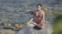 Beautiful woman relaxing alone at the beach, sitting in lotus posture - stock footage