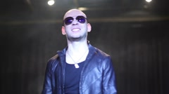 Bald guy in leather jacket with sunglasses sings among smoke Stock Footage