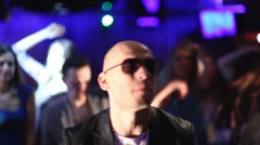 Bald man sings and young people out of focus dance in night club Stock Footage