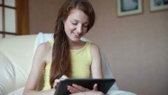 Young charming girl uses a tablet. Stock Footage