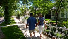 Mature Romantic Couple Walks Past Homes In Idyllic Neighborhood Stock Footage