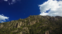Fast moving clouds over rocky mountains, shadows running Arkistovideo