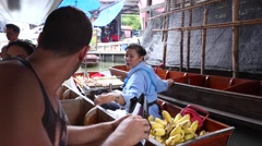 Thailand's most famous Floating Market. Woman sells some fruits to tourists. Stock Footage