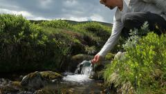 Man filling cup from a stream Stock Footage