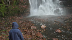 Raincoat at bottom of waterfall - stock footage