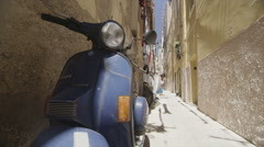 Vintage scooter parked in a side street of an Italian town on a summer day Stock Footage