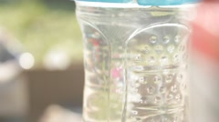 Water in bottle sparkles in sunlight Stock Footage
