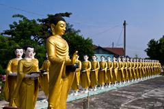 Statue of Buddha and disciples are alms round - stock photo