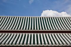 Roof Tiles white and green with blue sky - stock photo