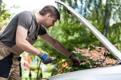 Mekaanikko käyttäen apukäynnistyskaapeleita aloittaa auton akku Kuvituskuvat