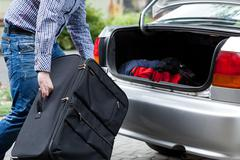 Man putting suitcases in car trunk for a journey Stock Photos