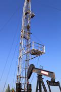 oil pump jack (sucker rod beam) and workover rig on sunny day - stock photo