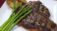 Grilled T-bone Steak with Potatoes and Asparagus Stock Footage