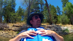 Man In Deep Thought Floats On River Or Lake Past Trees Stock Footage