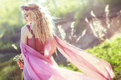 Beautiful blonde girl in pink long dress on a background of nature Stock Photos