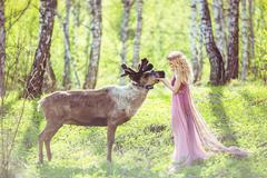 Girl in fairy dress and reindeer in the forest Kuvituskuvat
