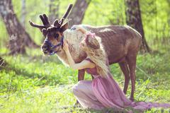Stock Photo of Portrait of a girl sitting in a fabulous dress next to a reindeer