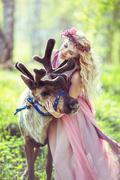 Stock Photo of Portrait of Beautiful girl hugging a reindeer