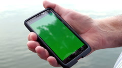 1880 Man Holding Smart Phone with Green Sceen next to Lake,HD Stock Footage