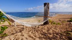 Hammock swaying in the breeze on sandy beach. Stock Footage