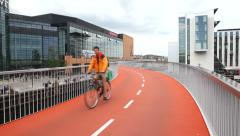 Red bike path passing Copenhagen Mall Stock Footage
