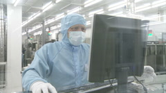A man wearing a mask and blue cap sits at a computer.keyboard gloves Stock Footage