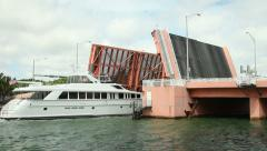 Yacht crossing under raised draw bridge Stock Footage