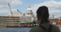 Woman looks over Thames at St Pauls rack focus 4K Stock Footage