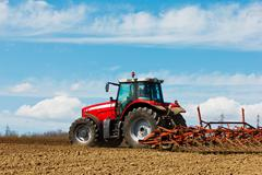 farmer plowing the field. cultivating tractor in the field. red farm tractor wit - stock photo