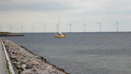 Stock Video Footage of Yellow boat passing wind turbines at sea