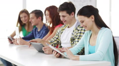 Smiling students with tablet pc at school Stock Footage