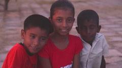 Portrait view of three local kids sitting on a beach in Matara, Sri Lanka. Stock Footage