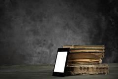 Smart-phone and old yellowed books Stock Photos