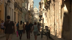 Domed Church at end of narrow, busy street in shade and sunshine Stock Footage