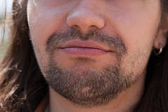 Part of face young European man with beard. - stock photo