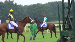 4k Jockeys and racing horses relaxing before the race at boxes Stock Footage