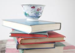 pile of used books with teacup - stock photo
