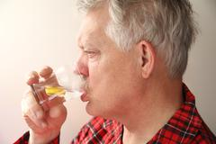 Ill senior man with soothing drink Stock Photos