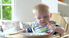 Baby Boy Eating Meal In In High Chair Stock Footage