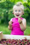 Child eating cherries Stock Photos