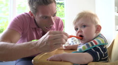 Father Feeding Baby Boy In High Chair Stock Footage