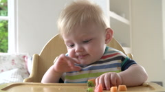 Baby Boy Eating Fruit In In High Chair Stock Footage