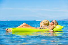 Young woman floating on raft Stock Photos