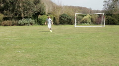 Young Boy Playing Football In Garden - stock footage