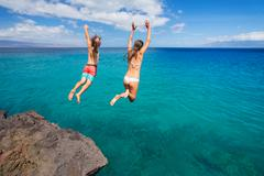 friends cliff jumping into the ocean - stock photo